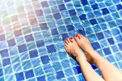 Härlig flicka som kopplar av i simbassängen, ben av kvinnan i vatten Royaltyfri Bild