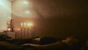 Härlig flicka som kopplar av på tabellen efter massagen i brunnsorten lager videofilmer