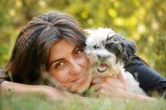 Härlig flicka som kramar hennes hund i berget Royaltyfri Bild
