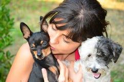 Härlig flicka som kramar två lilla hundkapplöpning Royaltyfri Foto