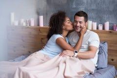 Härlig flicka som kysser hennes pojkvän i säng Royaltyfri Bild