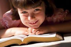 Härlig flicka som läser den heliga bibeln Royaltyfri Bild