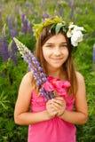 Härlig flicka som ler i en rosa klänning i lupinfält Royaltyfria Foton