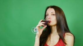 Härlig flicka som ler och lyfter exponeringsglas av vin i rostat bröd henne som bär i en röd ärmlös tröja Grön bakgrund stock video
