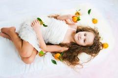 Härlig flicka som ligger bland tangerin Arkivbilder