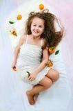 Härlig flicka som ligger bland tangerin Arkivfoto