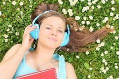 Härlig flicka som ligger i en äng och lyssnar till musik Arkivfoton