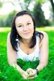 Härlig flicka som ligger på ett gräs Fotografering för Bildbyråer