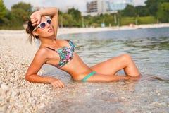 Härlig flicka som ligger på kusten och tar sunbath arkivfoto