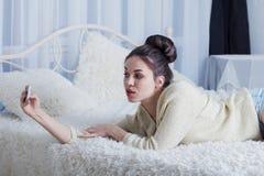 Härlig flicka som ligger på sängen och tar selfie Royaltyfria Foton