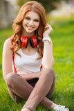Härlig flicka som lyssnar till musik på hörlurar Arkivfoton