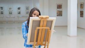 Härlig flicka som målar en bild på kanfas arkivfilmer