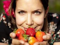 Härlig flicka som på våren luktar nya jordgubbar Royaltyfri Bild