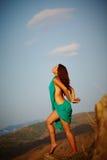 Härlig flicka som plattforer på ett klippbrants- Fotografering för Bildbyråer