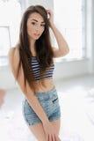 Härlig flicka som poserar i den vita studion Fotografering för Bildbyråer
