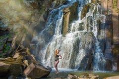 Härlig flicka som poserar i en hög vattenfall, absolut öde rödhårig manflicka i en vattenfall Arkivfoton
