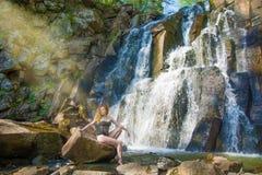 Härlig flicka som poserar i en hög vattenfall, absolut öde rödhårig manflicka i en vattenfall Arkivbilder