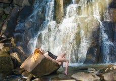 Härlig flicka som poserar i en hög vattenfall, absolut öde rödhårig manflicka i en vattenfall Arkivbild