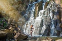 Härlig flicka som poserar i en hög vattenfall, absolut öde rödhårig manflicka i en vattenfall Royaltyfri Fotografi