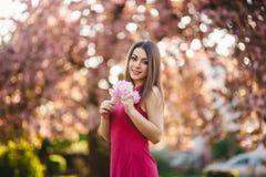 Härlig flicka som poserar till fotografen mot bakgrunden av blommande rosa träd Vår Sakura Royaltyfria Foton