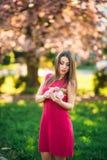 Härlig flicka som poserar till fotografen mot bakgrunden av blommande rosa träd Vår Sakura Royaltyfri Foto