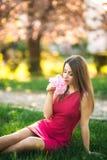 Härlig flicka som poserar till fotografen mot bakgrunden av blommande rosa träd Vår Sakura Royaltyfria Bilder