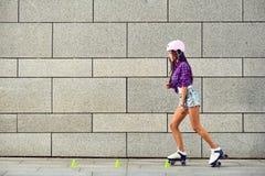 Härlig flicka som rollerblading på den stads- gråa bakgrunden i en parkera royaltyfria foton