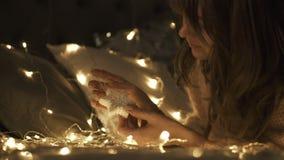 Härlig flicka som rotera en leksak för julsnöflingagarnering på säng Hon är lycklig arkivfilmer