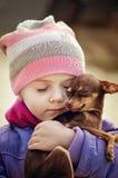 Härlig flicka som rymmer den lilla chihuahuahunden, kamratskapbegrepp Arkivfoton