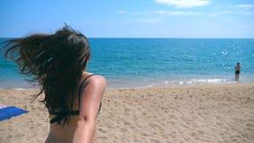 Härlig flicka som rymmer den manlig handen och spring på semesterortstranden till havet Följ som mig, drar skottet av den unga kv stock video