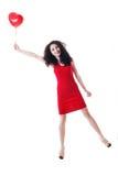 Härlig flicka som rymmer den röda ballongen Arkivbild