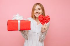 Härlig flicka som rymmer en röd hjärta, valentin- och gåvaasken i hennes händer, på en rosa bakgrund valentin för dag s royaltyfri fotografi