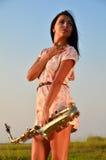 Härlig flicka som rymmer en saxofon i hans händer Royaltyfri Bild