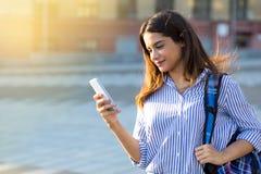 Härlig flicka som rymmer en telefon och att smsa ett meddelande som utomhus går och tycker om solig dag royaltyfri bild