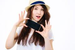 Härlig flicka som rymmer en telefon på vit bakgrund Royaltyfri Bild