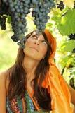 Härlig flicka som ser druvor Arkivbild