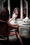härlig flicka som ser spegeln Arkivfoton