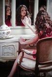härlig flicka som ser spegeln Arkivfoto