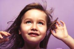 Härlig flicka som ser upp på purpurfärgad bakgrund Royaltyfri Foto