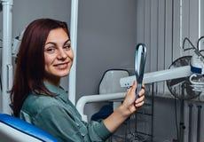 Härlig flicka som sitter i en tandläkarestol med spegeln i händer som ser kameran arkivbilder
