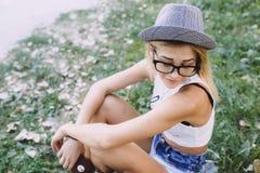 Härlig flicka som sitter och ser till sidan Arkivfoto