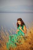 Härlig flicka som sitter på en klippa Royaltyfria Bilder