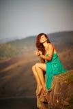 Härlig flicka som sitter på en klippa Royaltyfri Foto
