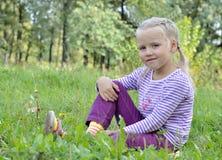 Härlig flicka som sitter på gräset Fotografering för Bildbyråer