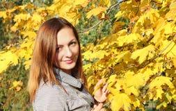 Härlig flicka som sitter på jordningen nära de gula sidorna, flickahöst i natur på en solig dag brun hårfärg in arkivfoton
