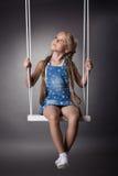 Härlig flicka som sitter på swing Royaltyfria Bilder