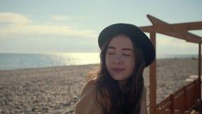Härlig flicka som sitter tyst på en strand stock video