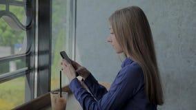 H?rlig flicka som sitter vid f?nstret med en telefon och en drink p? tabellen stock video