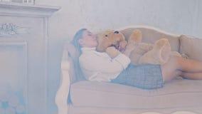 Härlig flicka som sover på soffan i en omfamning med en nallebjörn arkivfilmer