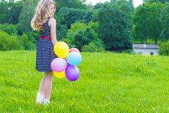 Härlig flicka som spelar med färgrika ballonger i sommardagen mot den blåa himlen Arkivfoto